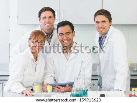 Group portrait of smiling scientists with tablet PC in the laboratory - stock photo