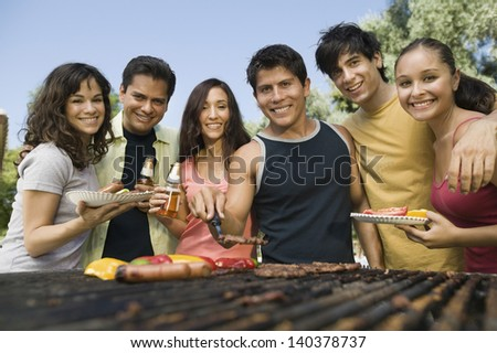 Group portrait of young people gathered around the grill at picnic - stock photo