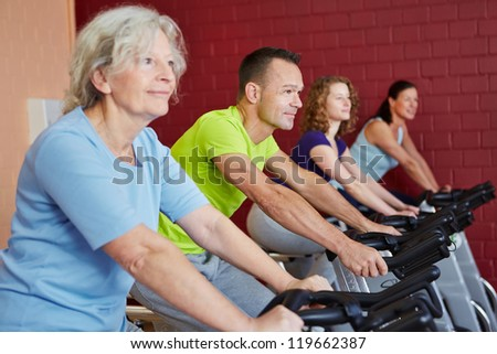 Group riding spinning bikes in a fitness class in health club - stock photo