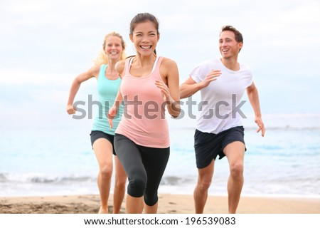 Group running on beach jogging having fun training. Exercising runners training outdoors living healthy active lifestyle. Multiracial fitness runner people working out together outside smiling happy. - stock photo