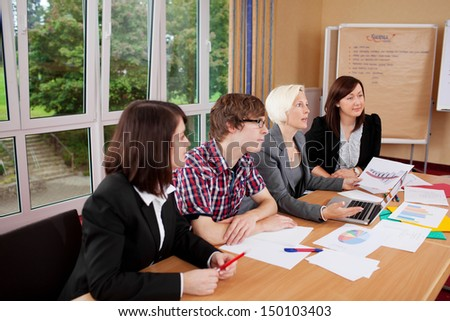 group sitting at table and listening to someone in a meeting - stock photo