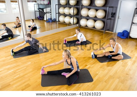 Group stretching exercises for muscle flexibility at fitness center - stock photo