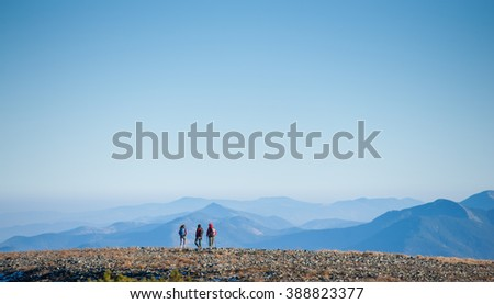Group/team of three young athletic people enjoying the view on the rocky mountain plato on their backpacking trip. Beautiful mountains on background. Healthy lifestyle concept. Rear view. Copy space - stock photo