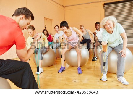 Group with active senior training with expanding band  - stock photo