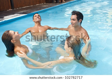 Group with four people forming a circle at aqua fitness in swimming pool - stock photo