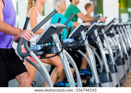 Group with senior and young men and women on elliptical treadmill trainer in fitness gym exercising - stock photo
