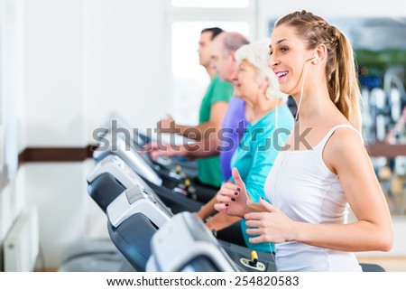 Group with senior and young men and women on treadmill in fitness gym running for sport - stock photo