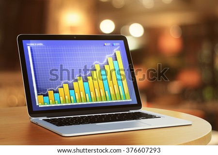 Growing business graph at laptop screen on round table - stock photo