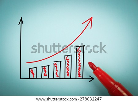 Growth graph is on blue paper with a red marker aside. - stock photo