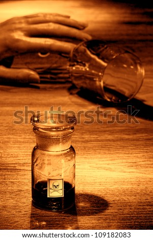 Gruesome murder crime scene of a dead woman hand holding a spilled drinking glass with empty poison bottle as forensic criminal evidence in rough grunge sepia - stock photo