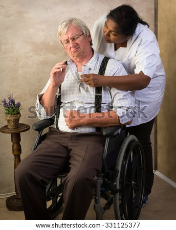 Grumpy old grandpa in nursing home receiving medication by a nurse - stock photo