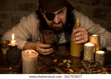 grumpy pirate with a bottle of rum sitting on a medieval table with a lot of candles - stock photo