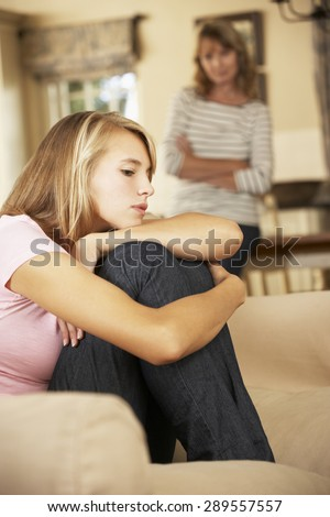 Grumpy Teenage Daughter Sitting On Sofa With Mother In Background - stock photo