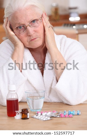 Grumpy woman taking her medication - stock photo