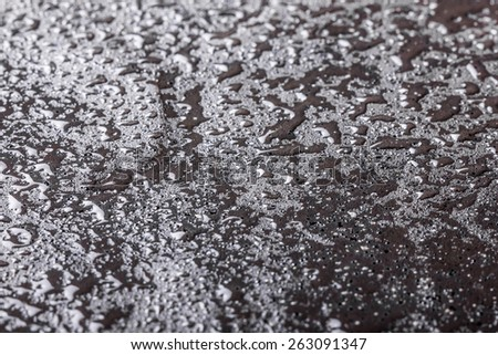 Grunge black surface with raindrops. - stock photo