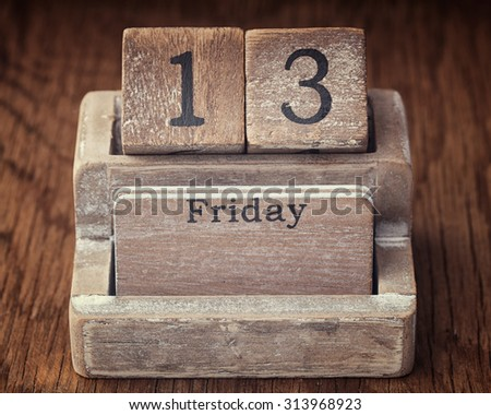 Grunge calendar showing Friday the thirteenth on wood background - stock photo