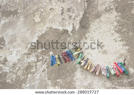 Grunge cement wall background texture with damaged pitted concrete and peeling plaster and rope with colorful plastic clothespin hanging on rope; Faded style effect - stock photo