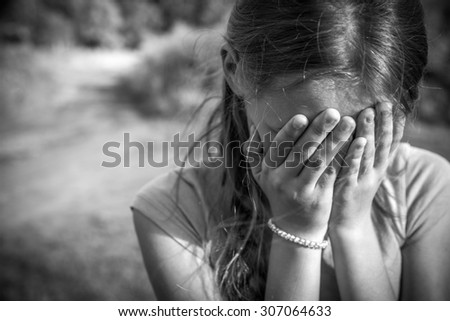 Grunge close-up portrait of a girl crying and covering her face  - stock photo