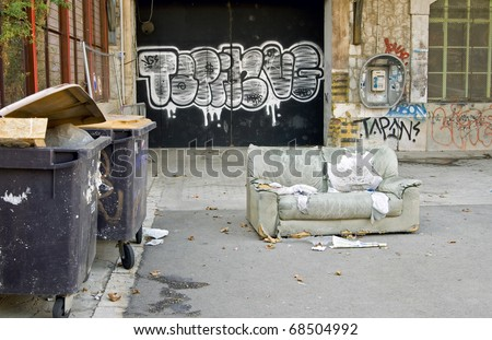 Grunge decor outdoors: very grunge decor outdoors with large garbage bins, old decrepit sofa, graffiti - stock photo