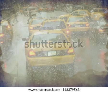 Grunge defocused Manhattan taxi cabs during the rain - stock photo