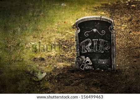 Grunge grave with tombstone shallow DOF  - stock photo