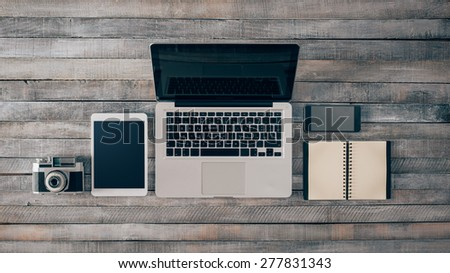 Grunge hipster wooden desktop with computer, digital tablet, vintage camera, smart phone and notebook, top view - stock photo