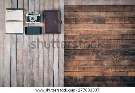 Grunge hipster wooden desktop with vintage camera, organizer, mobile and notebook, blank copy space - stock photo