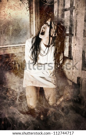 Grunge Horror Scene of a Woman Possessed Screaming Wearing a Straight Jacket - stock photo