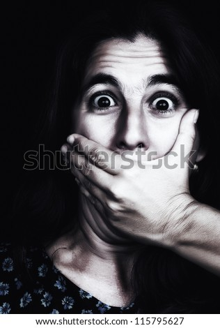 Grunge image of a frightened woman covering her mouth useful to illustrate gender violence or discrimination (on a black background) - stock photo