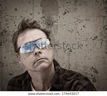 Grunge image of a Man with the Blue Sky reflected in his Glasses - stock photo