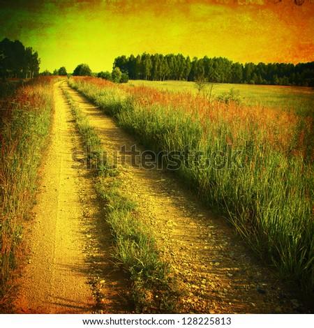 Grunge image of rural road at sunset. - stock photo