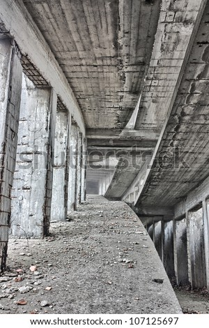 grunge interior of an abandoned building with rubble and debris - reinforced concrete construction in ruins - stock photo