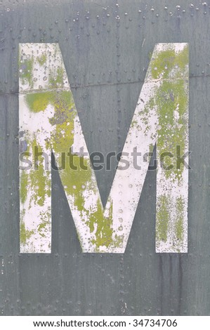 Grunge letter M painted on old metal surface with rivets - stock photo