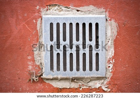 Grunge metal air grid on cracked wall. - stock photo