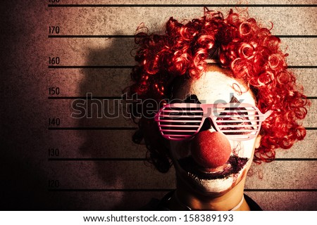 Grunge portrait of a funny clown criminal getting mug shot ID photo on police lines - stock photo