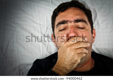 Grunge portrait of a sick hispanic man laying in bed covering his mouth to avoid coughing or vomiting - stock photo