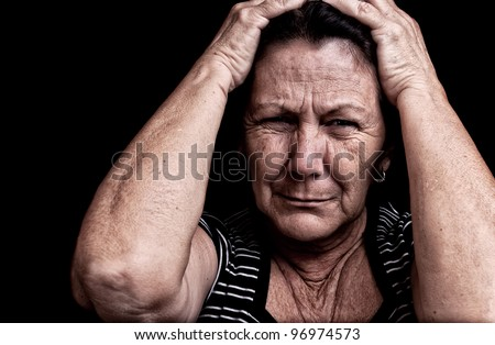 Grunge portrait of an old woman suffering from a headache with a desperate expression - stock photo