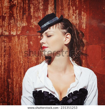 Grunge portrait of beautiful woman with closed eyes near rusty red wall. Steampunk style. - stock photo