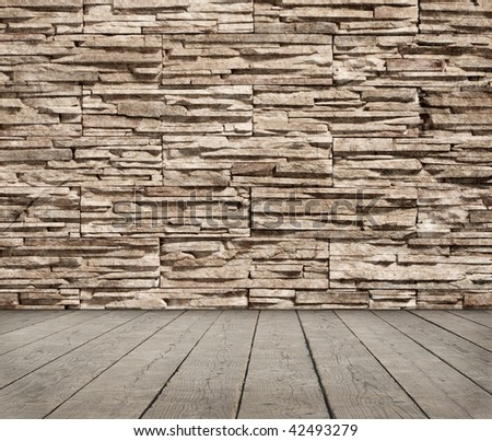 Grunge room with a stone wall - stock photo