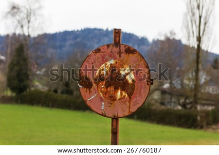 grunge stop sign in green fields - stock photo