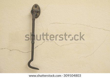 Grunged single gold hook over yellow concrete wall background - stock photo