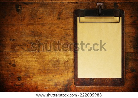 Grungy clipboard on old wooden surface, with plenty of copy space. - stock photo