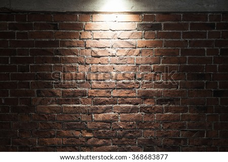 Grungy dark red brick wall with spotlight, background photo texture - stock photo