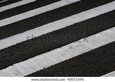 grungy, dirty view of asphalt with distinct white stripes - stock photo