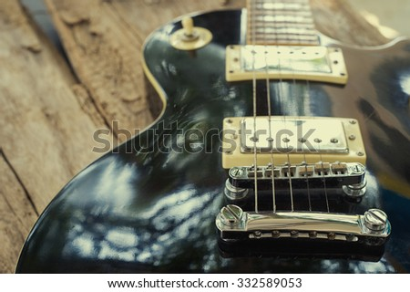 Grungy Electric guitar on wood and vintage effect tone. - stock photo