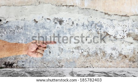 Grungy image of a hand with a pointing finger on a weathered mason wall, with blank space for text. - stock photo