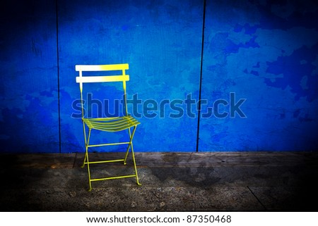 Grungy industrial blue wall with a yellow folding chair - stock photo