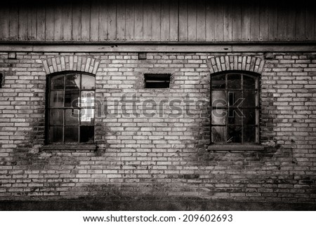 Grungy old barn with two broken windows - stock photo