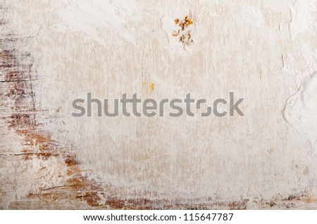 Grungy wooden board with beige and scratched plaster on the surface. - stock photo