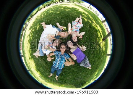 grupa students lie on the grass, photographed by fisheye - stock photo